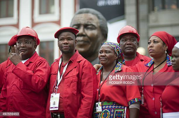 Members of the Economic Freedom Fighters pose for a photo in front a bust of Nelson Mandela at the South African parliament before for the first...