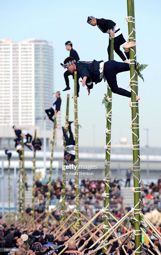 Members of the Edo Firemanship Preservation Association balance on top of bamboo ladders as they perform ladder stunts during the New Year's fire review conducted by the Tokyo Fire Department at Tokyo Big Sight on Janaury 6, 2013 in Tokyo, Japan.