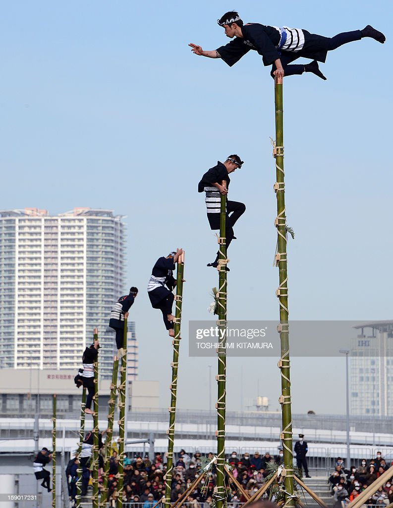 Members of the Edo Firemanship Preservation Association display their skills with stunts on the top of bamboo ladders at the annual new year fire review in Tokyo on January 6, 2013. A total of 2,800 fire fighters, 133 vehicles, 5 helicopters and 8 boats participated in the new year firefighting exercises.
