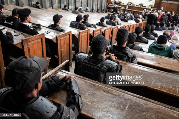 Members of the Egyptian security forces are seen seated on the benches at a makeshift courthouse in southern Cairo on December 2 during a trial...