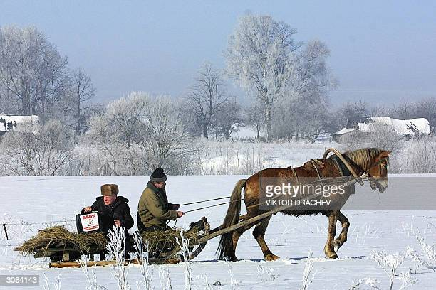 Members of the election commission from the polling station of Verhovie village some 40 km west of Smolensk travel on a sledge pulled by a horse on a...