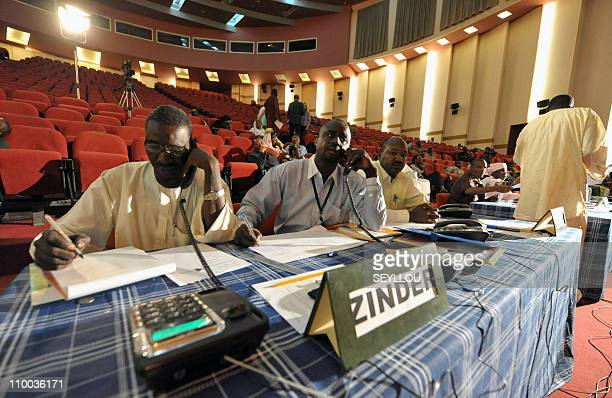 Members of the electoral commission make phone calls to obtain provisional results after Saturday's presidential runoff on March 13 on a TV set in...