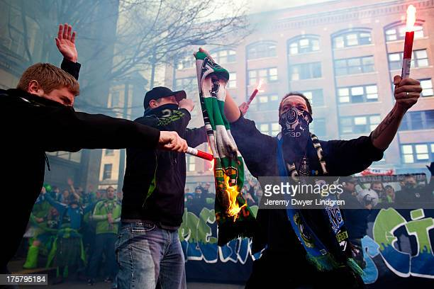 CONTENT] Members of the Emerald City Supporters a hardcore fan group backing Seattle Sounders FC soccer club burn a rival Portland Timbers scarf...