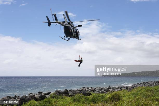 TOPSHOT Members of the emergency medical service evacuate by helicopter the body of a fisherman who was attacked and killed by a shark in SainteRose...