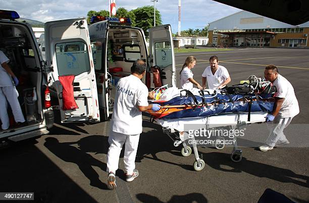 Members of the emergency medical service Samu carry a teenage victim of a motorcycle accident on the tarmac of Tahiti Faaa airport in Faaa French...