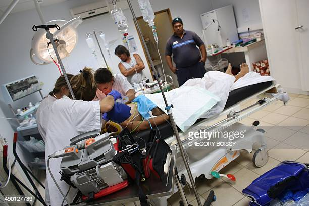Members of the emergency medical service Samu give medical care to a teenage victim of a motorcycle accident on May 11 2014 in the dispensary of Bora...