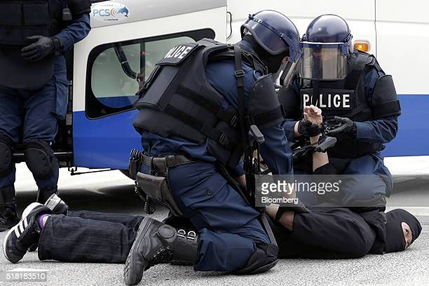 Members of the Emergency Response Team of Japan's Metropolitan Police Department restrain a man playing a role as a bus hijacker while they simulate...