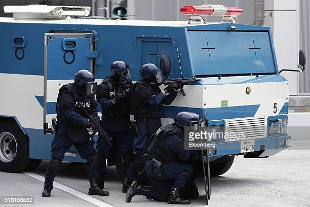 Members of the Emergency Response Team of Japan's Metropolitan Police Department simulate a bus hijacking and hostage crisis during a drill at a bus...