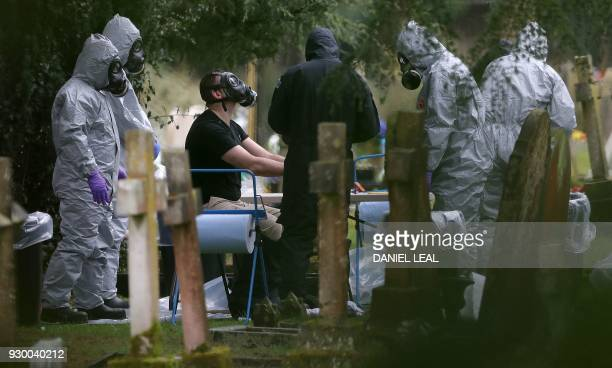 TOPSHOT Members of the emergency services and police help colleagues remove their protective suits as they work at the London Road Cemetery in...