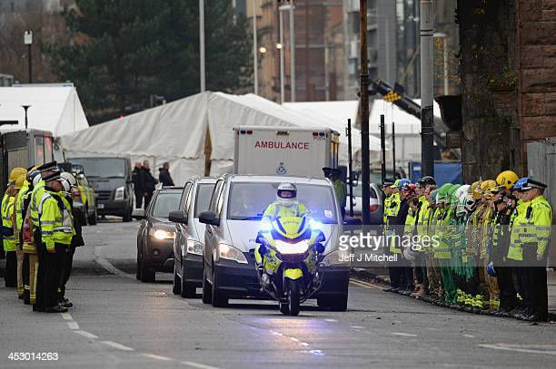 Members of the emergency services and rescue workers form a guard of honour for ambulances removing bodies from The Clutha bar where a police...