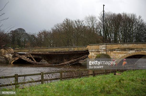 Members of the emergency services assess the damage to a bridge caused by floodwater over the River Wharfe in Tadcaster in northern England on...