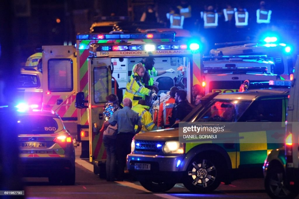 Members of the emergency services attend to victims of a terror attack on London Bridge in central London on June 3, 2017. Armed police opened fire during what they described as a 'terrorist' attack in central London Saturday after reports of stabbings and a van ploughing into pedestrians just days ahead of a general election. /