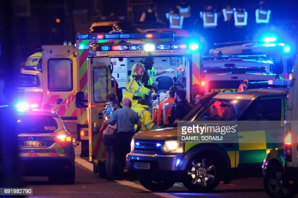 Members of the emergency services attend to victims of a terror attack on London Bridge in central London on June 3 2017 Armed police opened fire...