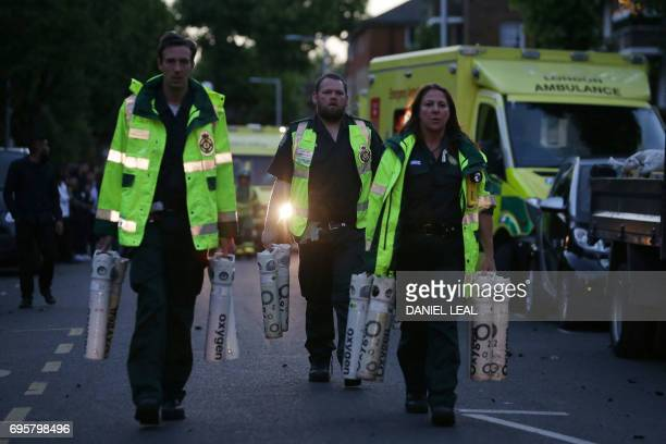 TOPSHOT Members of the emergency services carry oxygen tanks as a huge blaze engulfs Grenfell Tower a residential tower block on June 14 2017 in west...