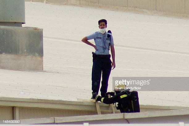 Members of the emergency services climb on the roof at the scene of a fire at the Villaggio mall on May 28, 2012 in Doha, Qatar. A fire started at...