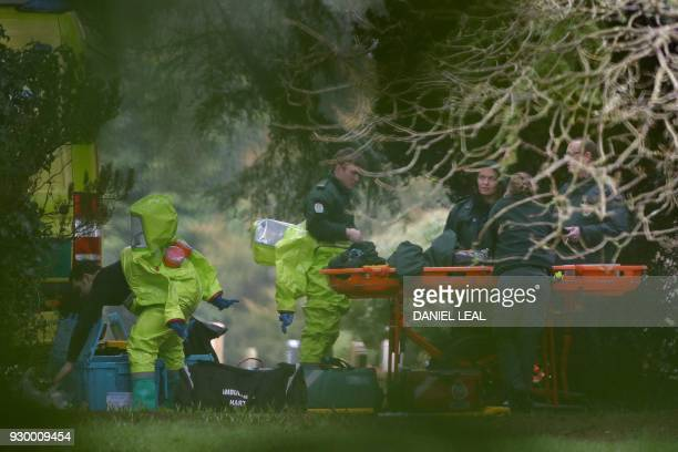 TOPSHOT Members of the emergency services don their green biohazard suits as they prepare to work at the London Road Cemetery in Salisbury southern...
