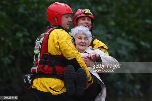 Members of the emergency services evacuate an elderly resident from flooded house by boat after the River Taff burst its banks in Nantgarw south of...