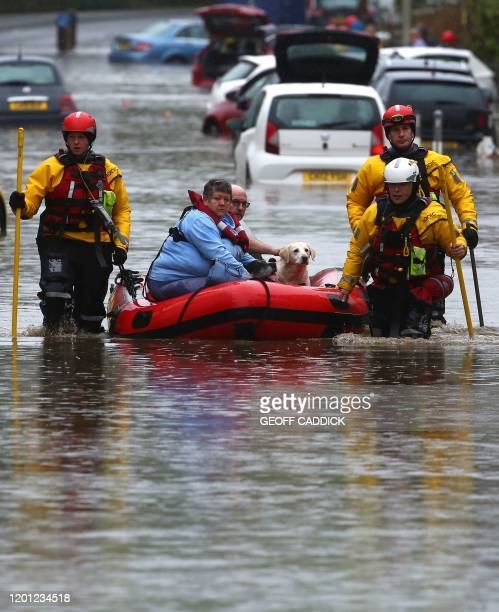 Members of the emergency services evacuate residents and their dogs from flooded houses by rescue boat after the River Taff burst its banks in...