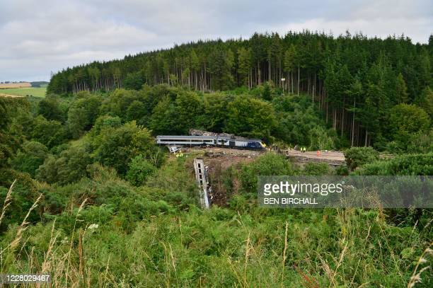 Members of the emergency services inspect the debris and derailed carriages at the scene of the train crash near Stonehaven in northeast Scotland on...