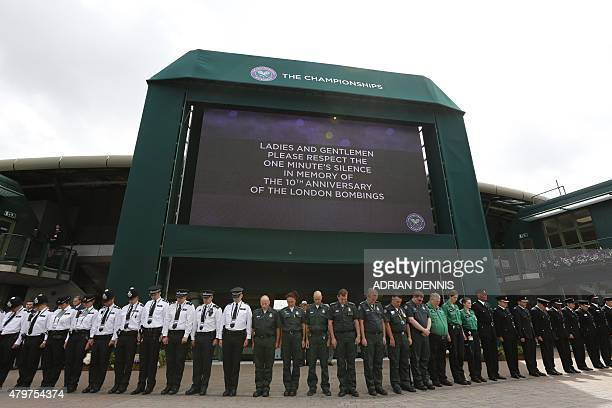 Members of the emergency services stand in a line under the big screen at the back of No 1 Court to observe a minute's silence in memory of the 52...