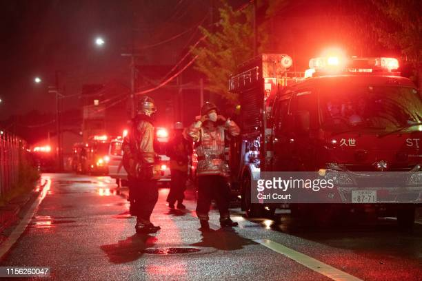 Members of the emergency services stand next to a fire truck after attending an arson attack at Kyoto Animation Co studio on July 18, 2019 in Kyoto,...