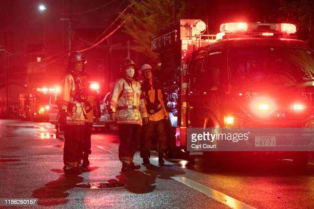 Members of the emergency services stand next to a fire truck after attending an arson attack at Kyoto Animation Co studio on July 18 2019 in Kyoto...
