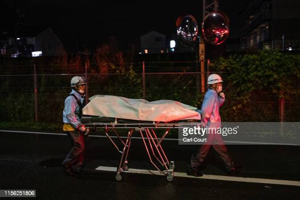 Members of the emergency services wheel a gurney along a road near Kyoto Animation Co studio after the building was set ablaze by an arsonist on July...