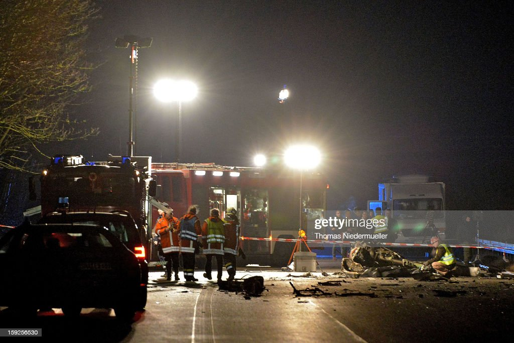 Members of the emergency services work at the scene of a helicopter wreckage after it crashed onto the A6 highway on January 10, 2013 near Schwabisch Hall, Germany. According to police the helicopter struck a nearby power line and exploded, killing the pilot and leaving one vehicle driver with minor injuries.