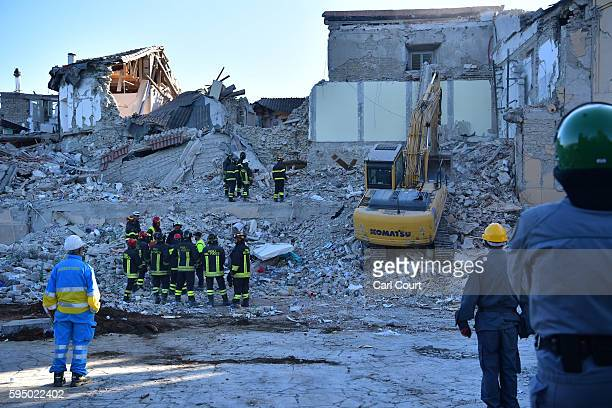Members of the emergency services work in the remains of buildings that collapsed after being struck by an earthquake on August 25 2016 in Amatrice...