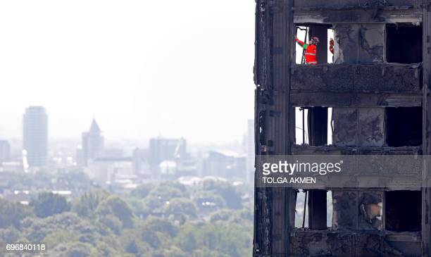 Members of the emergency services work inside the charred remnains of the Grenfell Tower block in Kensington west London on June 17 follwing the June...