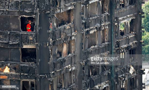 Members of the emergency services work on the middle floors of the charred remnains of the Grenfell Tower block in Kensington west London on June 17...