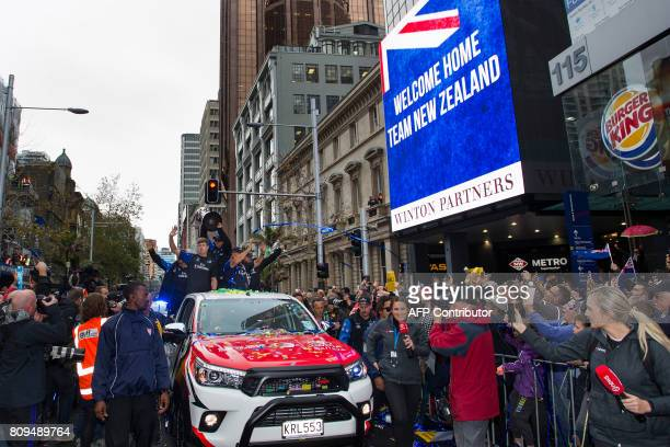 Members of the Emirates Team New Zealand parade the America's Cup yachting trophy through the streets of Auckland on July 6 2017 Team New Zealand...