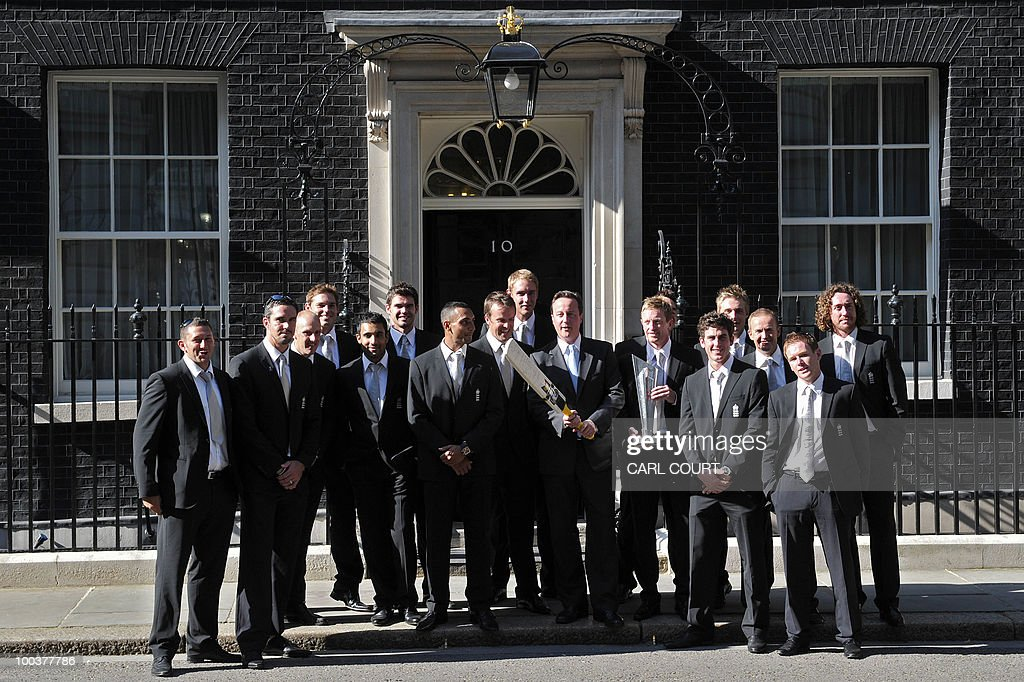 Members of the England Twenty20 Cricket World Cup winning team pose with British Prime Minister David Cameron (holding bat) outside 10, Downing Street, after meeting him inside for a reception following their success at the tournament in London on May 24, 2010. AFP PHOTO/Carl Court.