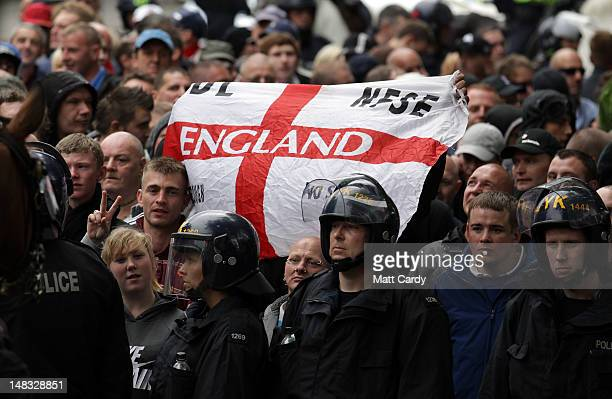 Members of the English Defence League display a England flag as they are escorted by police through Bristol on July 14 2012 in Bristol England A...