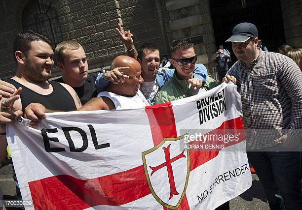 Members of the English Defence League pose for a photograph with EDL leader Tommy Robinson outside the Old Bailey in London on June 6 2013 The EDL...