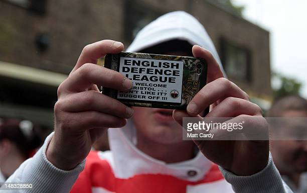 A members of the English Defence League takes a photograph as he prepares to march through Bristol on July 14 2012 in Bristol England A large police...