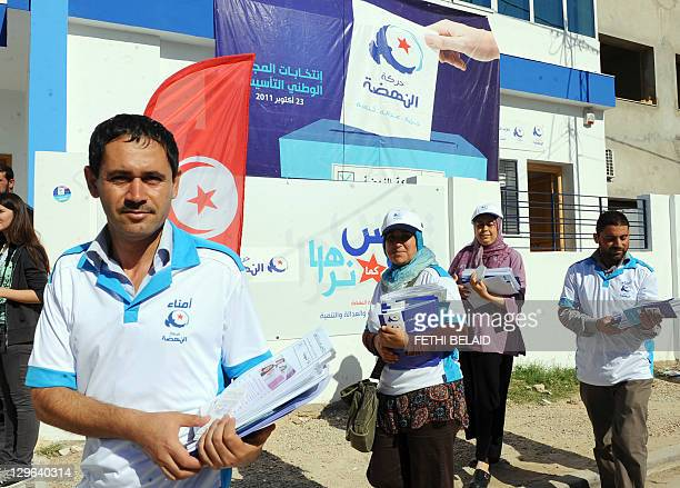 Members of the Ennahdha Islamist movement distribute electoral leaflets in front of the headquarters of the party on October 19 2011 in Ariana near...
