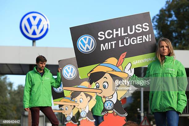 Members of the environmental action group Greenpeace hold up Pinocchio placards during a protest outside the Volkswagen AG headquarters in Wolfsburg...