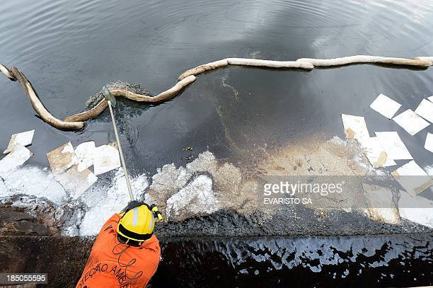 Members of the Environmental Protection Team from the fire department assembles an oil barrier trying to contain an oil spillage on the surface of...