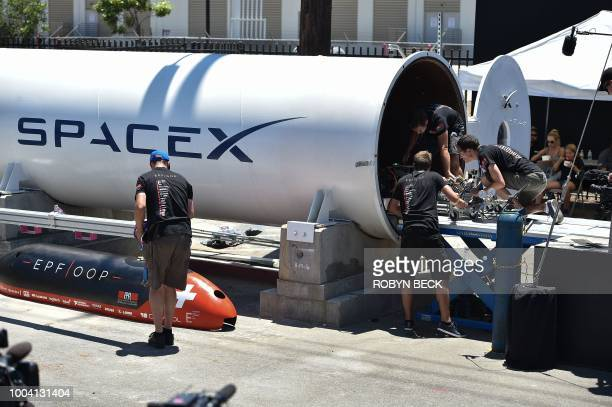 Members of the EPFL Hyperloop team from the Ecole Polytechnique Federale de Lausanne in Switzerland make final adjustments to their pod before...