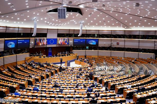 Members of the EU Parliament arrive and sit in an empty hemicycle at the beginning of the plenary session which is reduced to a single day due to the...