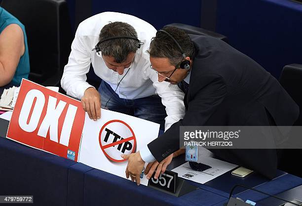 Members of the European Parliament set up a sign reading word No and a sign with the crossedout acronym of the Transatlantic Trade and Investment...