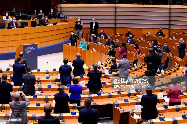 Members of the European Parliament stand up to applaud German Chancellor Angela Merkel after her speech during a plenary session at the European...