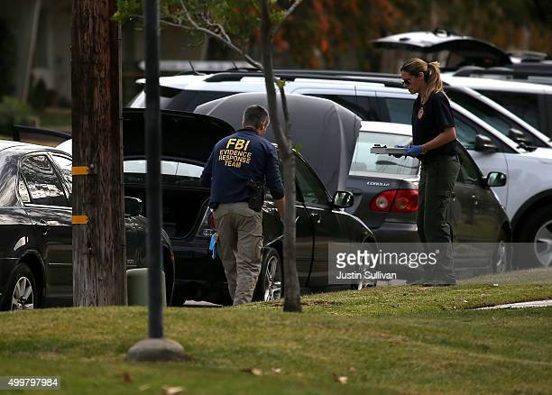 Members of the Evidence Response Team from the Federal Bureau of Investigation examine a car that allegedly belonged to Syed Farook on December 3...