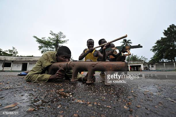 Members of the exSeleka rebels pose with their fake weapons at late Centrafrican emperor JeanBedel Bokassa's palace in Beringo on March 3 2014...