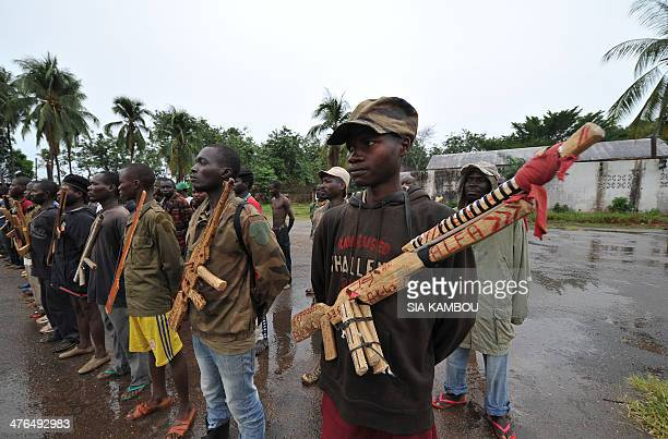 Members of the exSeleka rebels pose with wooden weapons in front of late Centrafrican emperor JeanBedel Bokassa's palace in Beringo on March 3 2014...