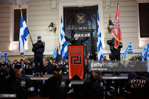 Members of the extremeright Golden Dawn party stand around a stage while the leader of the party Nikolaos Mihaloliakos delivers a speech on February...