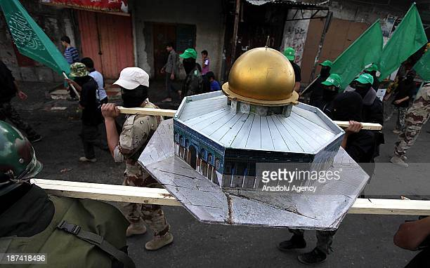 Members of the Ezzeddin al-Qassam, the military wing of Hamas, carry a model of Dome of the Rock as they march during an anti-Israel protest on the...