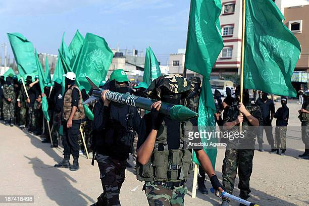 Members of the Ezzeddin al-Qassam, the military wing of Hamas, march during an anti-Israel protest on the first anniversary of Israel's Operation...
