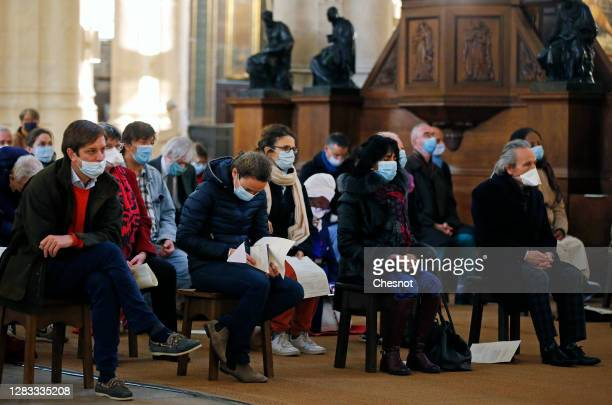 Members of the Faithful wear protective face masks while attending an All Saints Day mass conducted by Archbishop of Paris Michel Aupetit at the...